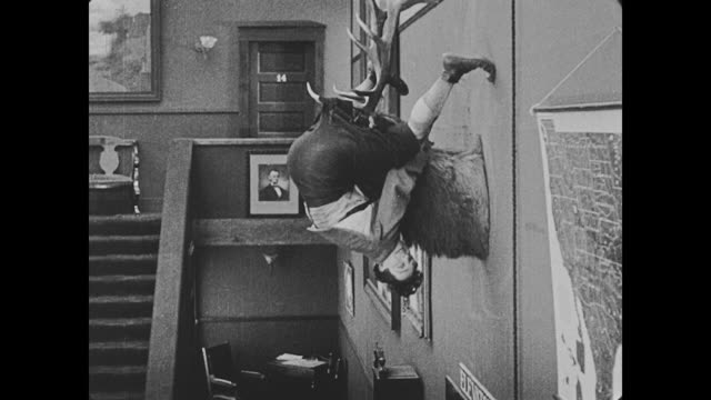 1918 bellman's (buster keaton) pants are caught on antler's of a deer head that hangs in hotel, his pants tear, releasing bellman as he bounces on a piece of wood that is stuck underneath the elevator and has created a catapult - stuffed stock videos & royalty-free footage
