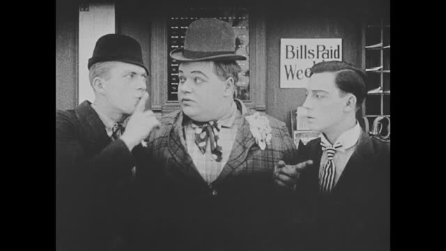 1918 bellmen (fatty arbuckle, buster keaton), and their supervisor are dressed nicely and  greet miss cutie cuticle (alice lake) who arbuckle pulls away when she talks to the supervisor - buster keaton stock videos and b-roll footage