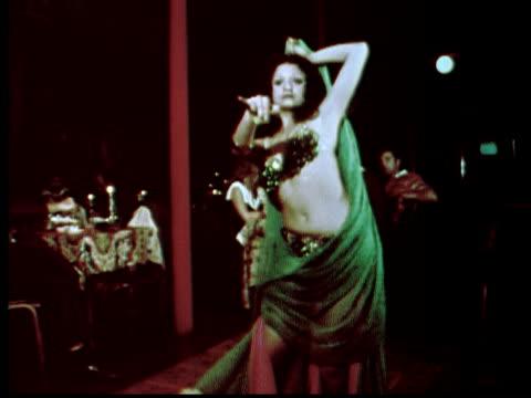1976 MONTAGE Belly dancer twirling. People applauding / Philadelphia, Pennsylvania, USA