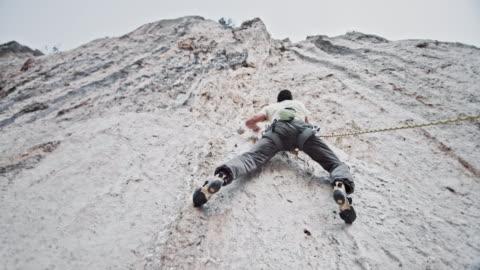 vídeos y material grabado en eventos de stock de a continuación un hombre escalador subiendo un acantilado vertical blanco - actividad al aire libre