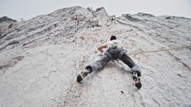Below a male rock climber ascending a vertical white cliff