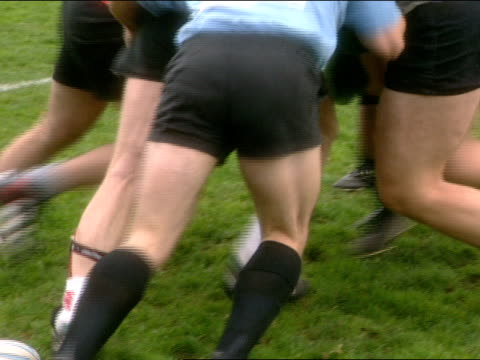 male twirling rugby ball in hands; tracking rugby football player w/ ball & two other teammates running into other players holding padding, ball... - protective sportswear stock videos & royalty-free footage