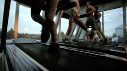 Below view of athletic people jogging on treadmills in a gym. Slow motion.