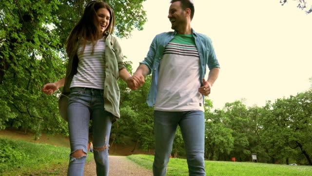 Unter Ansicht von glücklichen paar Hand in Hand und laufen in der Natur.