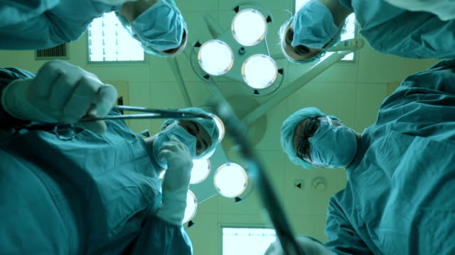 below view of team of surgeons cooperating while performing a surgery. fast motion. - general practitioner stock videos & royalty-free footage
