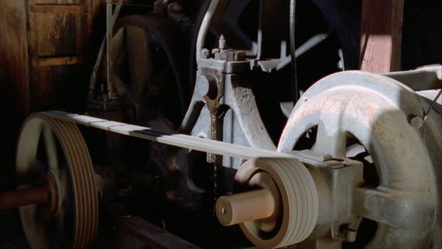 a belt turns a cog on an antique machine. available in hd. - antique stock videos & royalty-free footage