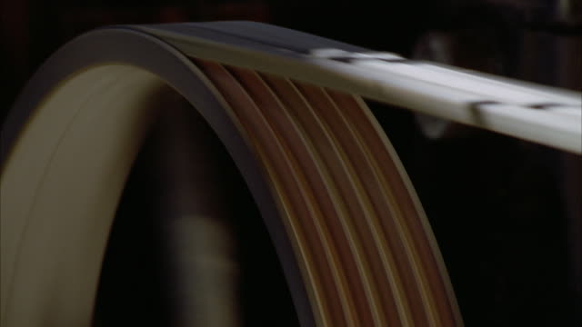 A belt turns a wheel on an antique machine. Available in HD.