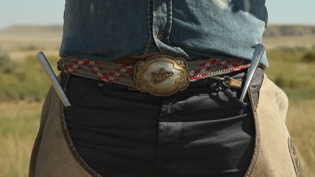 A belt with a metal buckle on a cowboy