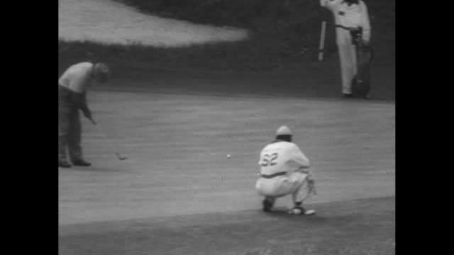 vídeos de stock, filmes e b-roll de ben hogan misses putt in masters tournament as caddy watches in foreground / members of gallery walk past the leader board inscribed masters at... - green de golfe