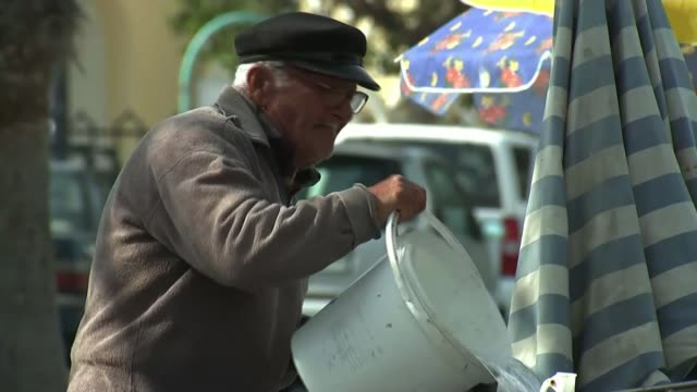 police appeal for mystery caller to get in touch elderly greek man emptying bucket of water houses amongst greenery - 提訴点の映像素材/bロール