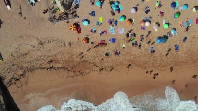 vídeos de stock e filmes b-roll de benagil's beach / algarve, portugal - apanhar sol