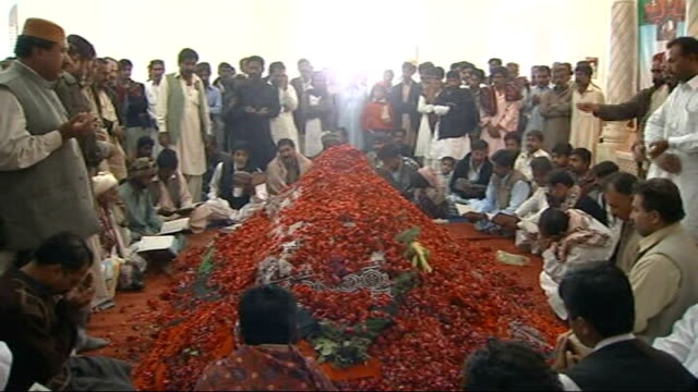 son bilawal named as her successor pakistan naudero larkana int coffin of benazir bhutto covered in red rose petals and surrounded by mourners male... - mourner stock videos & royalty-free footage