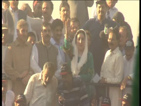 stockvideo's en b-roll-footage met benazir bhutto surrounded by supporters waves towards camera - omgeven