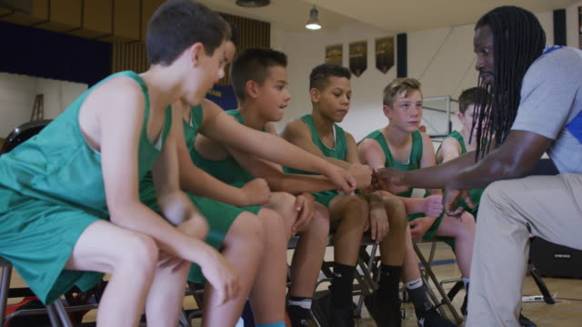 vidéos et rushes de banc de primaire âgés athlètes mettre mains ensemble pour un bravo - serré