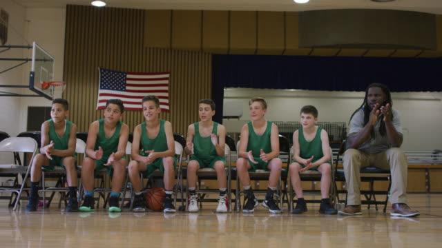 vídeos de stock, filmes e b-roll de banco de atletas de basquetebol elementar bater palmas para os jogadores na quadra - banco assento