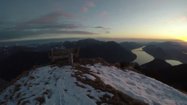 Bench on snowy Swiss mountain peak at sunset