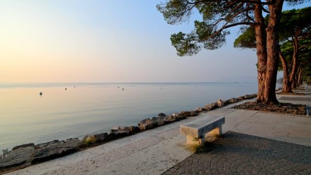 bench on the lakeshore at sunset, lazise, verona, lake garda, lago di garda, veneto, italy - lakeshore stock videos & royalty-free footage