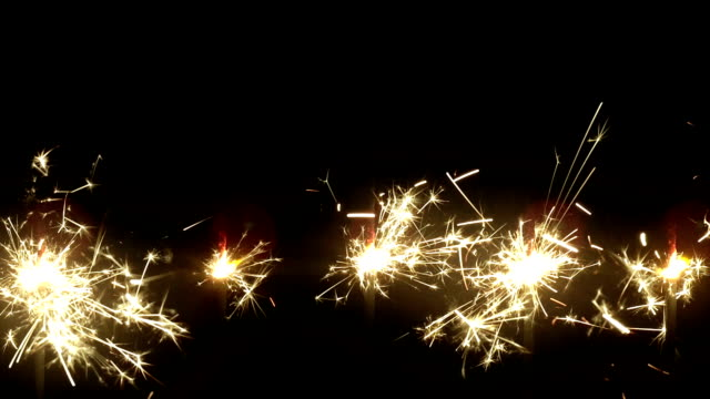 bengal light with bright sparkles on black background - pyrotechnic effects stock videos & royalty-free footage