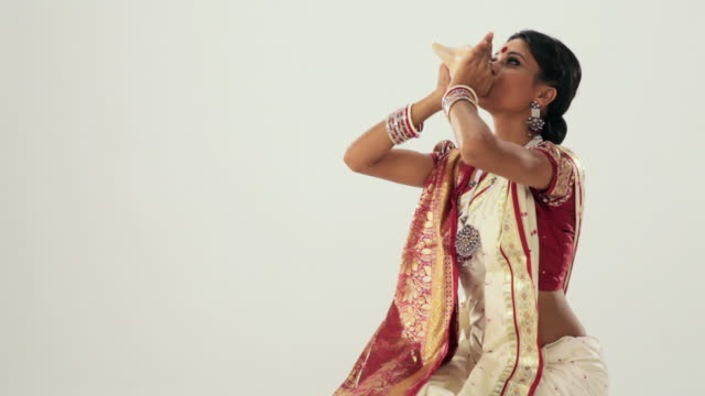 Bengali girl blowing a conch shell