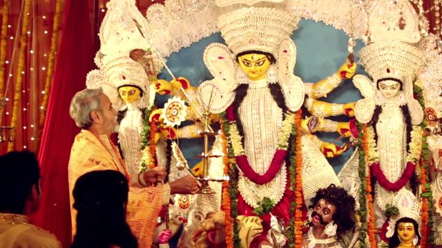 bengali priest worshipping in durga puja festival, delhi, india - figura femminile video stock e b–roll