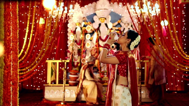 vídeos de stock, filmes e b-roll de bengali woman blowing conch shell in durga puja festival, delhi, india - concha parte do corpo animal