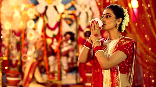 Bengali woman blowing conch shell in durga puja festival, Delhi, India