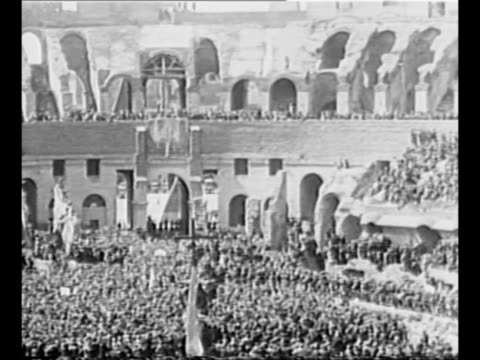benito mussolini addresses crowd inside the colosseum he wears civilian clothing / ws int colosseum with crowds cheering mussolini / 1940 pov from... - benito mussolini stock videos & royalty-free footage