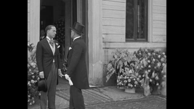 benito mussolini italian leader stands outside house wearing top hat and formal jacket galeazzo ciano who is about to wed mussolini's daughter edda... - benito mussolini bildbanksvideor och videomaterial från bakom kulisserna