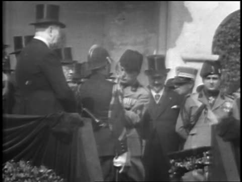 benito mussolini pins medal on policeman who kisses him on both cheeks / rome - benito mussolini stock-videos und b-roll-filmmaterial