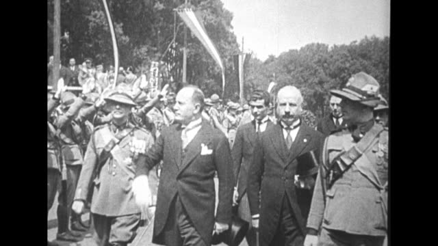 benito mussolini wearing a morning coat walks in italian street with others issues fascist salute at crowd alongside / italian soldiers march pass... - benito mussolini bildbanksvideor och videomaterial från bakom kulisserna
