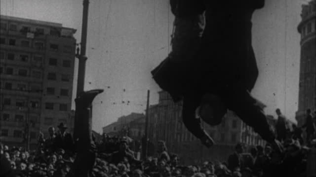Benito Mussolini's and other executed Fascists bodies being hung upside down on Piazza Loreto / Milan Italy