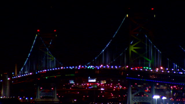 benjamin franklin bridge w/ different colored lights billboards lights in philadelphia bg out/in focus urban city - benjamin franklin stock videos & royalty-free footage