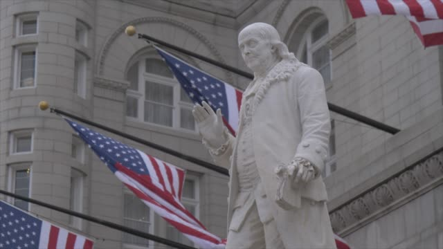 benjamin franklin statue and us flags in front of former old post office pavilion, washington dc, united states of america, north america - postamt stock-videos und b-roll-filmmaterial