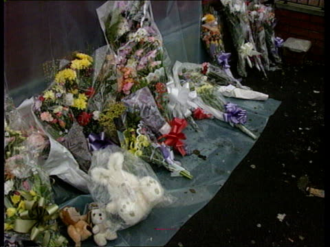 benji stanley murder; )nao england: manchester: moss side: side plastic sheet over front of shop where benji was murdered tcms flowers on bottom of... - side view stock videos & royalty-free footage