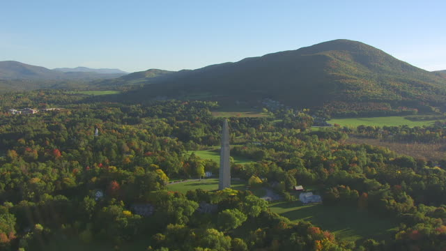 WS AERIAL POV Bennington Battle Monument in forest area with mountain in background / Bennington, Vermont, United States