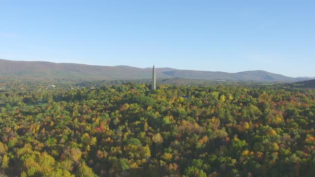 WS AERIAL POV Bennington Battle Monument with forest area / Bennington, Vermont, United States