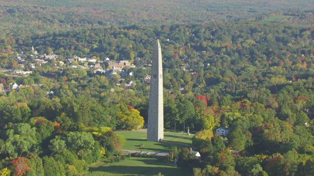 ws aerial pov bennington battle monument with forest area / bennington, vermont, united states - vermont stock-videos und b-roll-filmmaterial