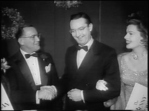 vídeos y material grabado en eventos de stock de benny goodman shaking hands with steve allen at premiere of the benny goodman story / news - mujer con grupo de hombres