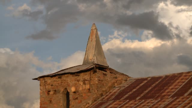 a bent tin roof covers the steeple of a deteriorating old stone church in madagascar. available in hd. - steeple stock videos & royalty-free footage