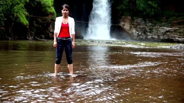 bent yoga posture near waterfall - postura video stock e b–roll