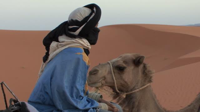 MS Berber guide sitting on camels in Erg Chebbi desert, Morocco