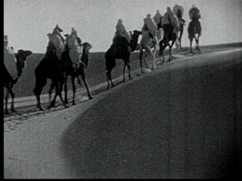 1925 B/W WS Berber nomads riding in camel caravan climbs up sand dune in Sahara desert / Tunisia