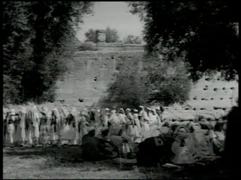 vídeos de stock, filmes e b-roll de berber people gathered outside in circle, men moving up/down clapping hands, chanting sot, one male w/ hand drum, women in bangled headresses, veils,... - 1951