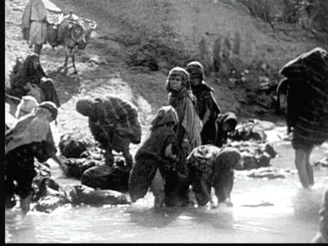 1925 b/w ws berber women + children doing laundry + bathing in pool of water / nefta, tunisia - 1925 stock videos & royalty-free footage