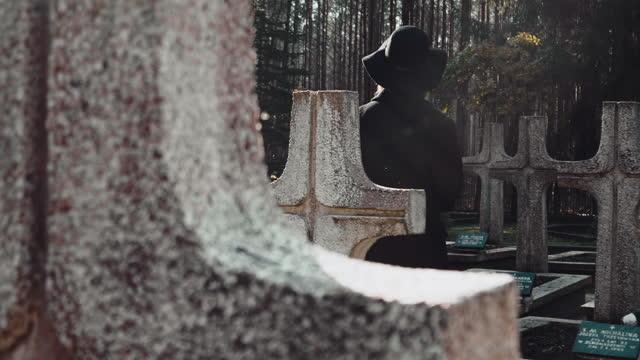 vídeos y material grabado en eventos de stock de mujer afligida de negro tomando rojo se levantó a la tumba. vista trasera - luto
