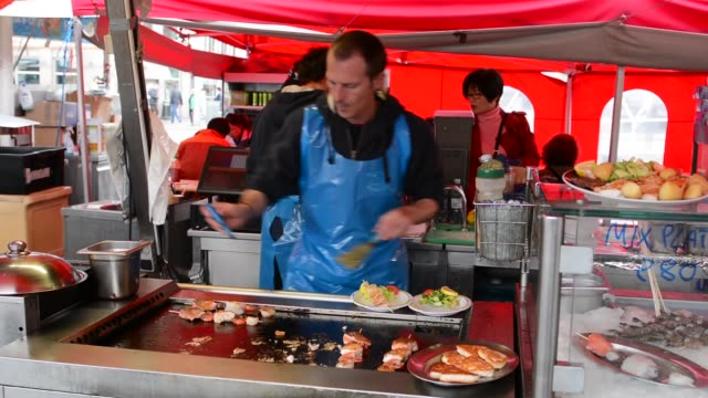 Bergen Norway seafood outdoor cafe cook prepares seafood for tourists in  BRYGGEN  MR-10