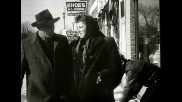 bergman walking down snow covered streets as villagers sweep the streets as part of weekly tradition / bergman shaking hands with shop propriator. - 毛皮のコート点の映像素材/bロール