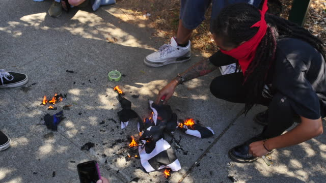 protesters burn a thin blue line american flag that honors fallen police in ohlone park in berkeley a huge crowd gathered nearby at martin luther... - anti fascism stock videos & royalty-free footage