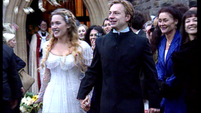 berkshire reading all saints church ext winslet and then husband jim threapleton out of church after wedding ceremony and confetti thrown over them - kate winslet stock-videos und b-roll-filmmaterial