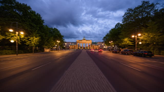 berlin brandenburg gate modern dynamic summer dusk to night hyperlapse with street lights on dramatic clouds and traffic - berlin stock videos & royalty-free footage